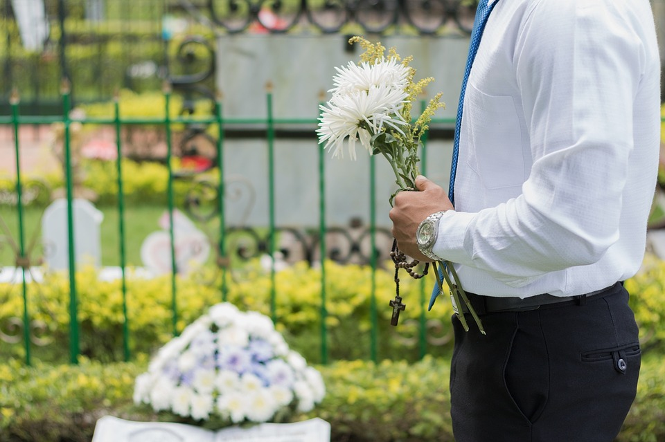 Simple funeral- man holding flowers at a funeral
