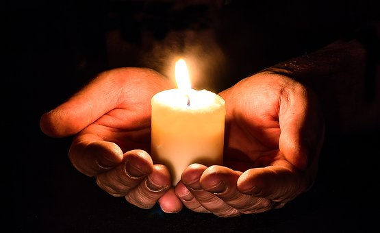 Coping with grief over Christmas- hands holding a candle